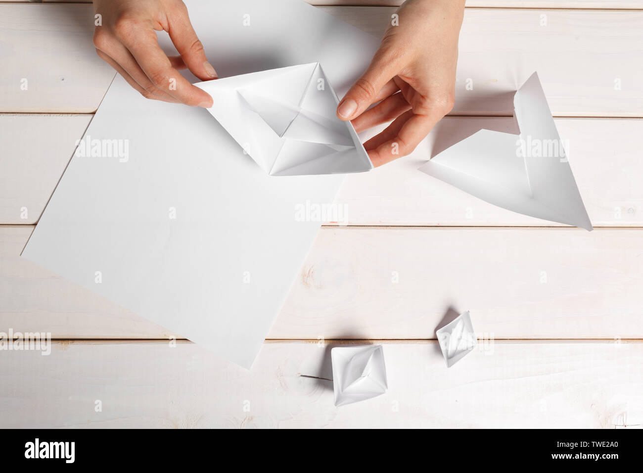Process of handcrafting origami paper boat - Stock Image