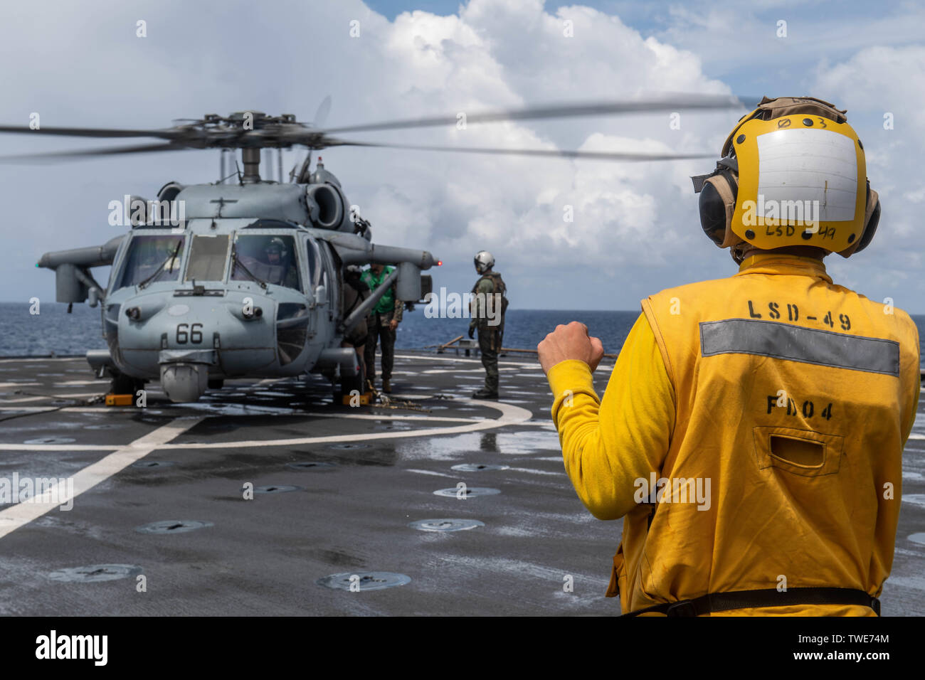 190615-N-HD110-0106  SOUTH CHINA SEA (June 15, 2019) Sailors observe an MH-60 Sea Hawk helicopter, attached to Helicopter Sea Combat Squadron (HSC) 21, as it lands on the flight deck of the Harpers Ferry-class amphibious dock landing ship USS Harpers Ferry (LSD 49). Harpers Ferry is part of the Boxer Amphibious Ready Group (ARG) and 11th Marine Expeditionary Unit (MEU) team and is deployed to the U.S. 7th Fleet area of operations to support regional stability, reassure partners and allies, and maintain a presence postured to respond to any crisis ranging from humanitarian assistance to conting - Stock Image