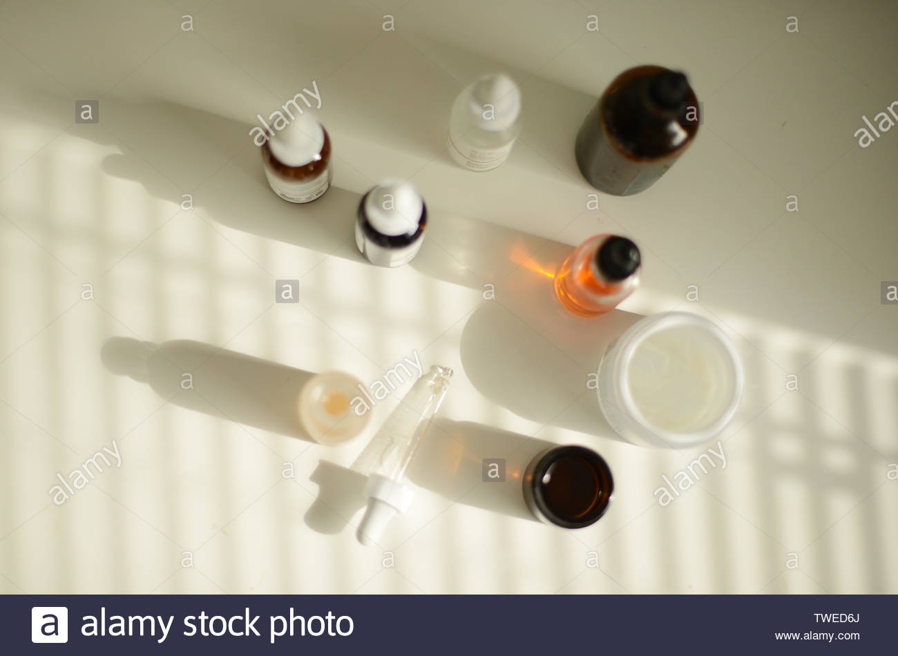 make-up and skin care products on a white table in a beautiful sunlight coming in through blinds - Stock Image