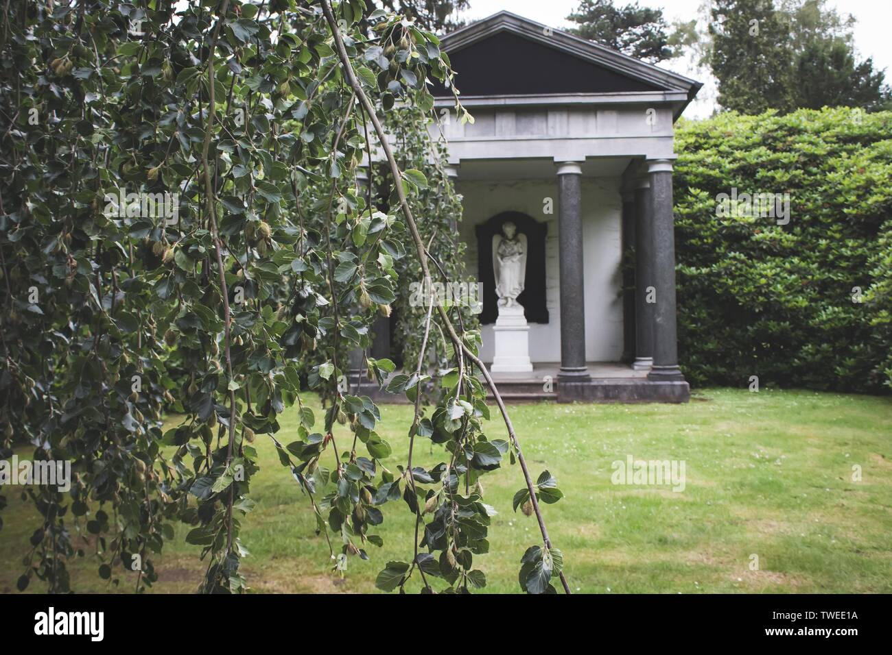 Beautiful old mausoleum behind a willow tree, seen in Hamburg Ohlsdorf, the world´s biggest garden cemetery Stock Photo