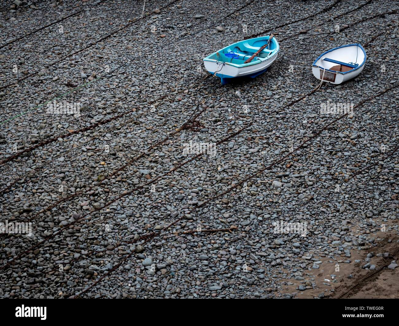 Two rowing boats lying on top of chains on a pebble beach - Stock Image