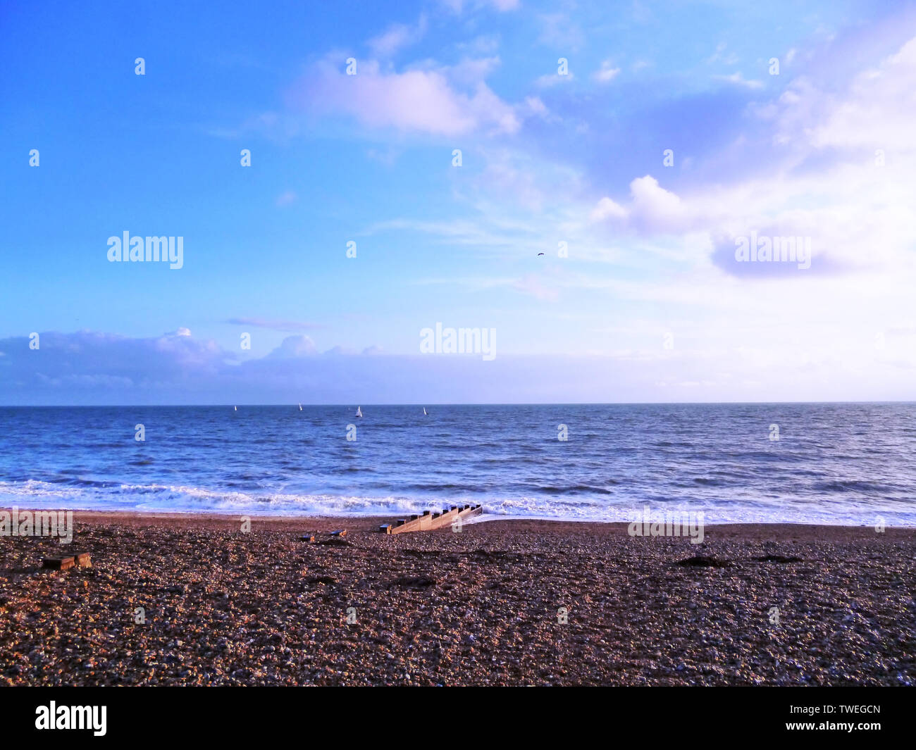 Beautiful panoramic view of English Channel sea with sailing boats at sunset in Sussex. Stock Photo