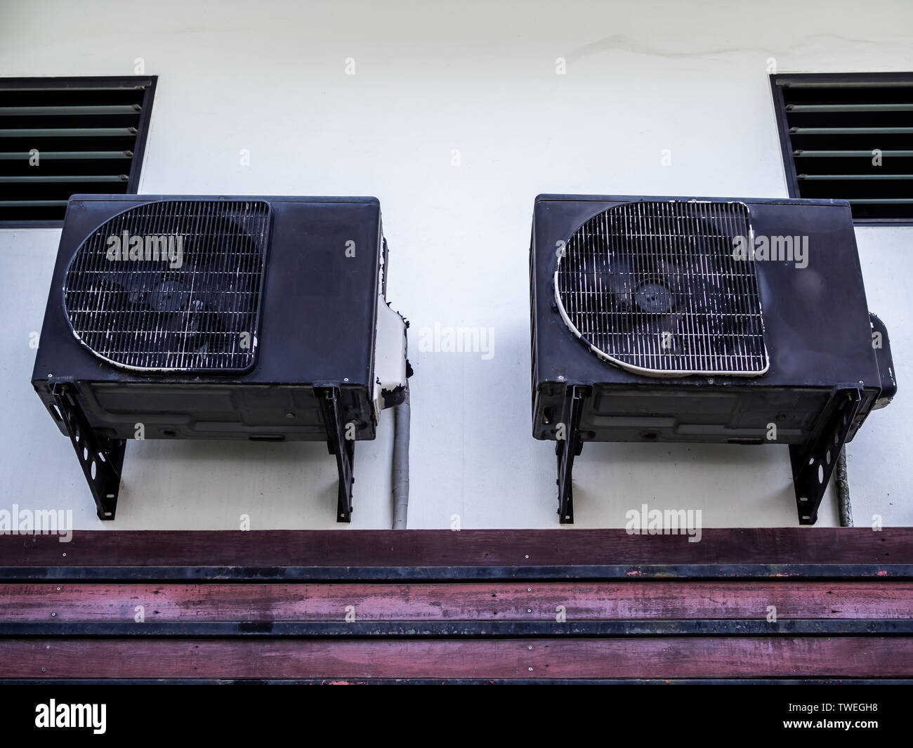Two old black air conditioner compressors on white wall outside the house. Stock Photo