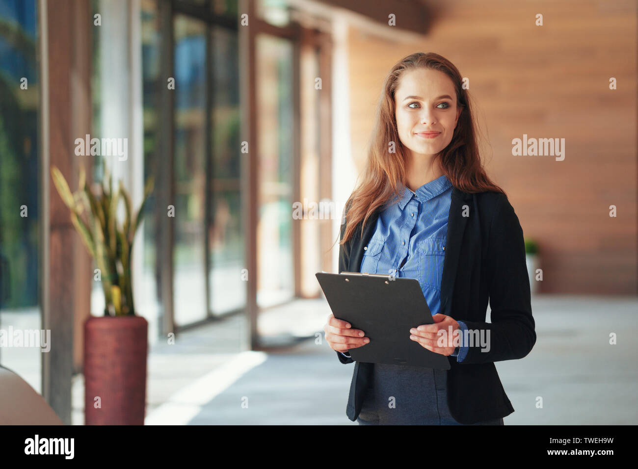 Happy beautiful business woman with clipboard in the office. - Stock Image