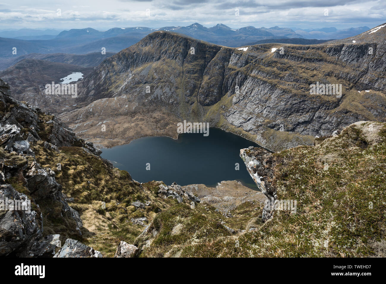 Loch a Choire Ghranda and the distant Fannaichs from the southern cliffs of Cona Mheall - Stock Image