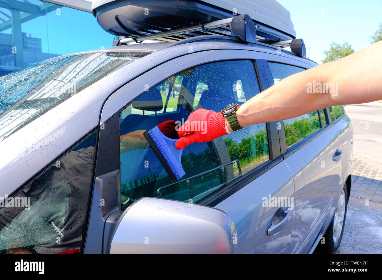 A man with a rubber scraper removes the remains of water from the glass after washing the car. Car wash. Self-service washing complex. High pressure c Stock Photo