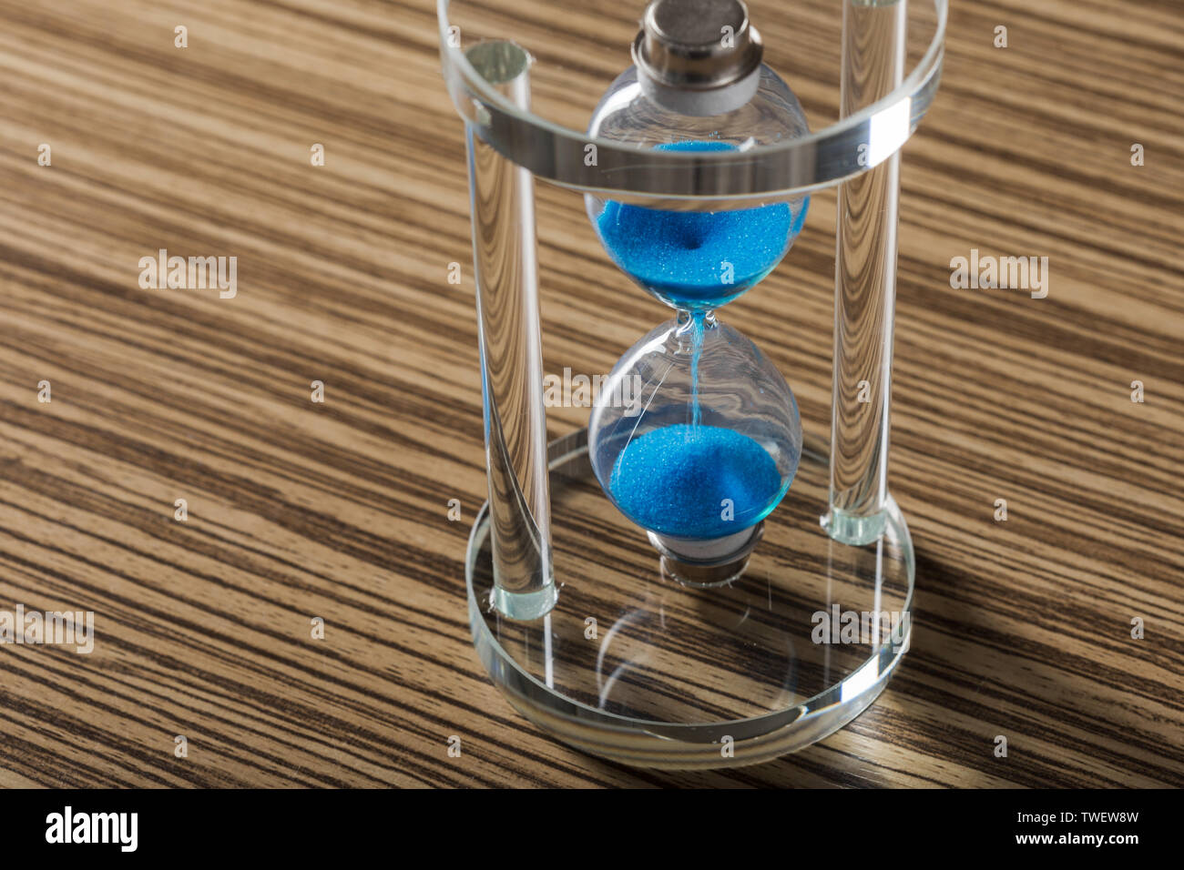 Time is passing. Blue hourglass close up - Stock Image