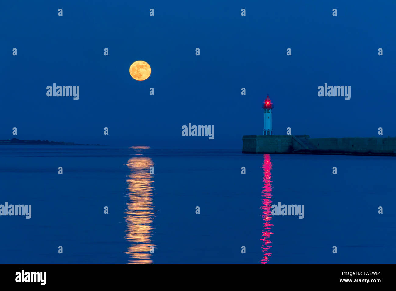 Full moon reflected next to the lighthouse in the water of the port of Almeria. - Stock Image