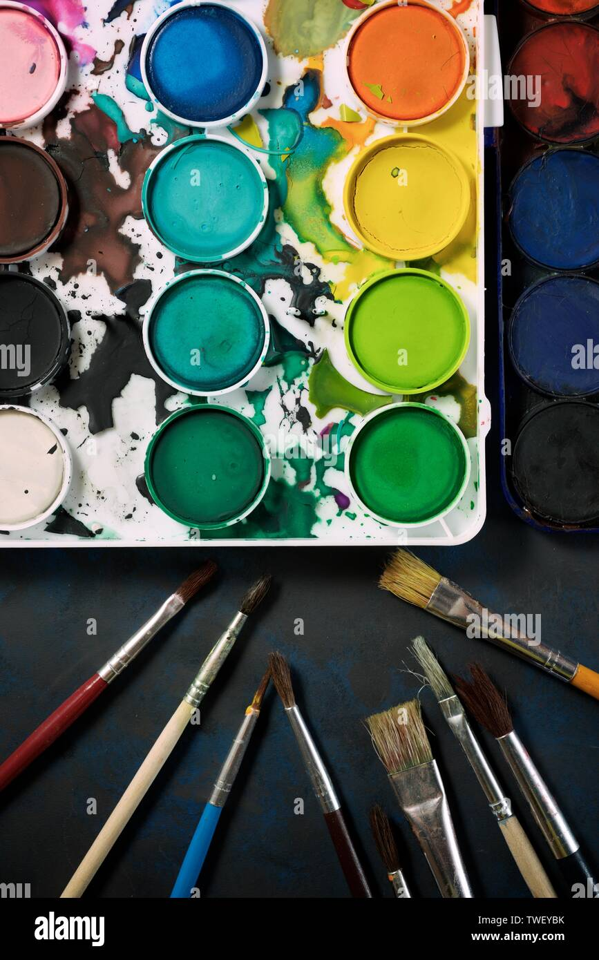 Box of watercolors and brushes on a table. Stock Photo