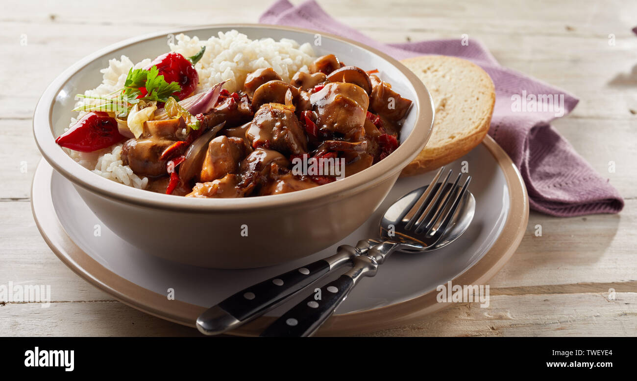 Bowl filled with white rice and seasoned meat on top of plate holding piece of bread. Plate and bowl sitting on wooden table. Stock Photo