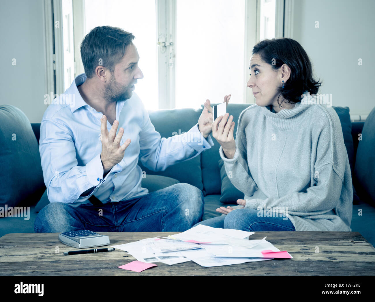 Stressed angry young couple arguing over credit card debts while accounting home finance paying bills mortgage bank statements and expenses feeling de - Stock Image