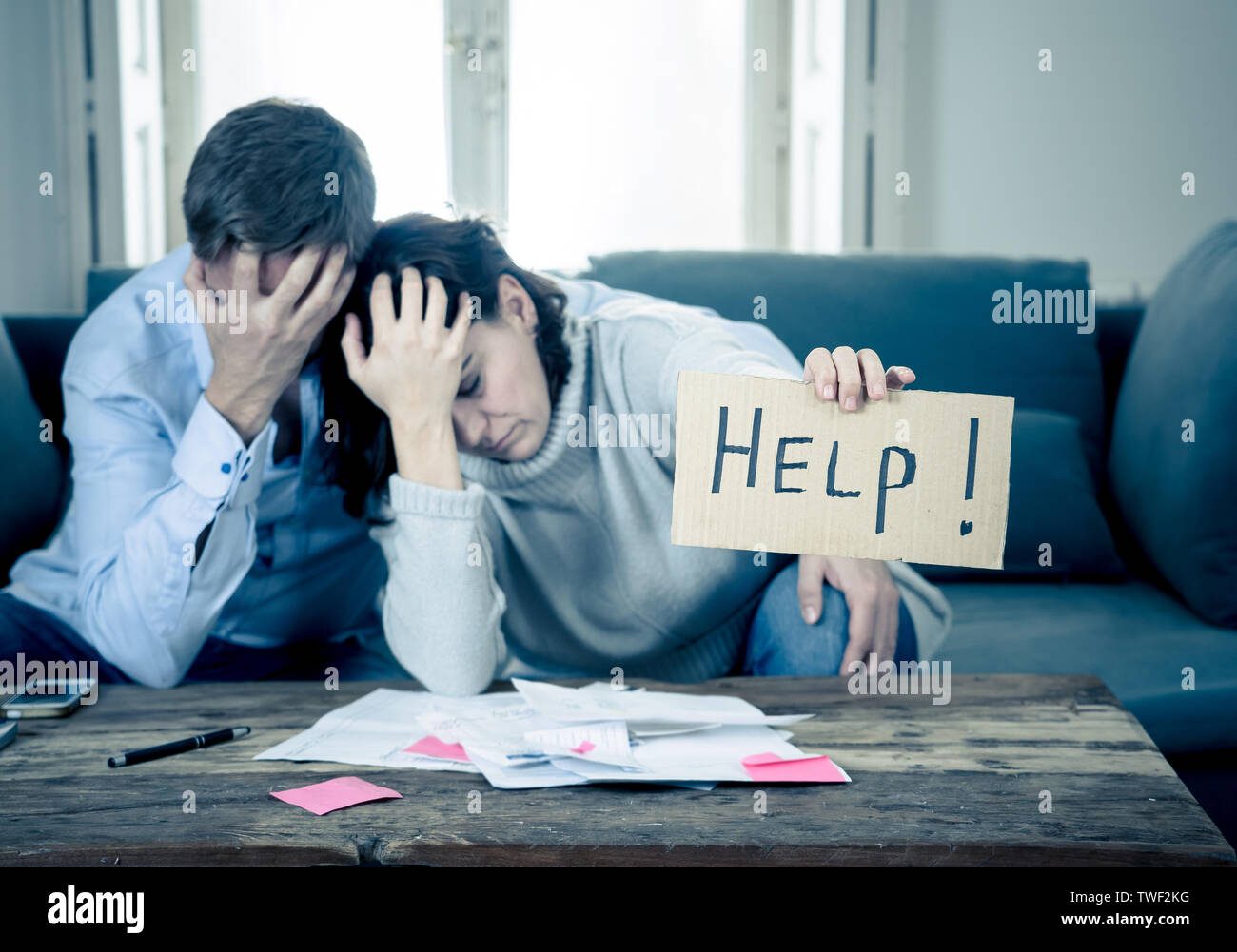 Stressed young couple needing help in accounting home finance paying bills mortgage bank statements and expenses feeling desperate having so many debt - Stock Image
