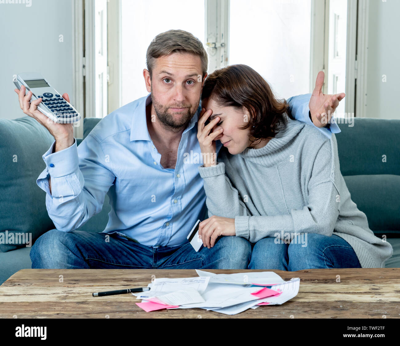 Stressed young couple accounting home finance paying bills mortgage bank statements and expenses feeling desperate having so many debts in bad financi - Stock Image