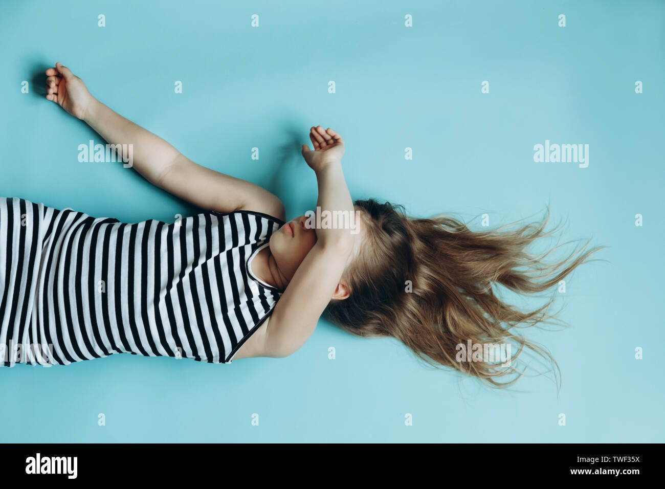 Girl laying on blue background covering face. Child sleeping flat lay top view. Having rest, relaxing. Childhood memories. Beautiful flowing hair. Simple minimalist background, wallpaper Stock Photo