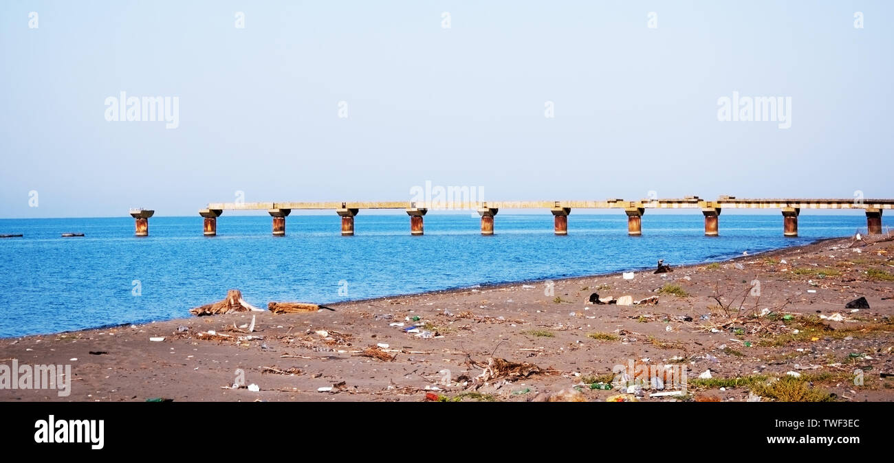 Old ruined pier and dirty beach of the black sea - Stock Image