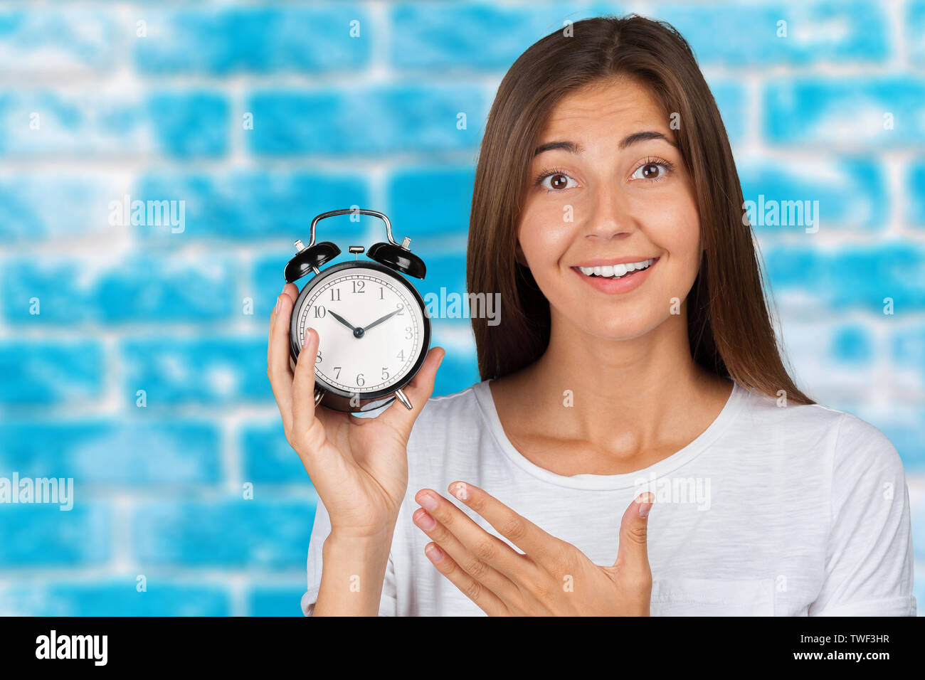 Smiling woman holding alarm watch - Stock Image