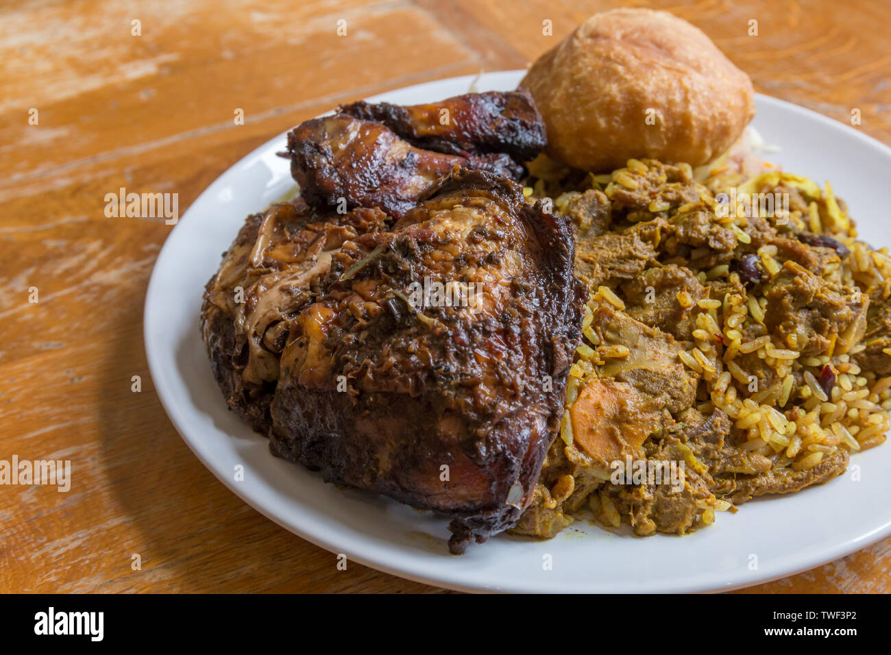 Jamaican food.  Traditional Jamaican curried goat, jerk chicken and fried dumpling with rice and peas - Stock Image