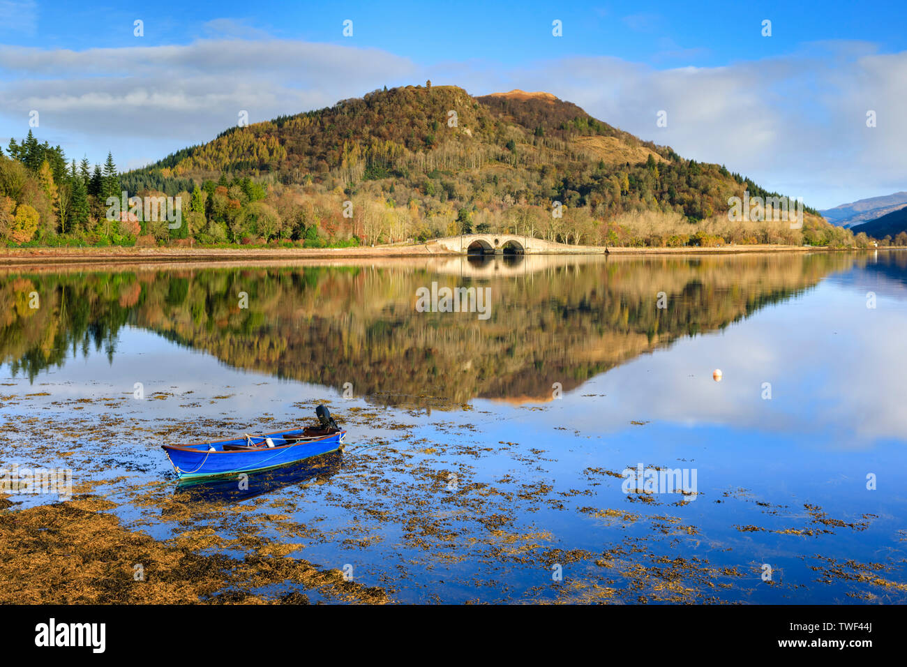 A boat and Dun na Cuaiche reflected in Inveraray Harbour. - Stock Image