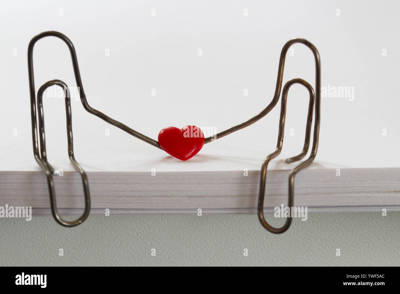 paper clips with heart symbolizing a person sitting on a stack of white paper. love concept Stock Photo