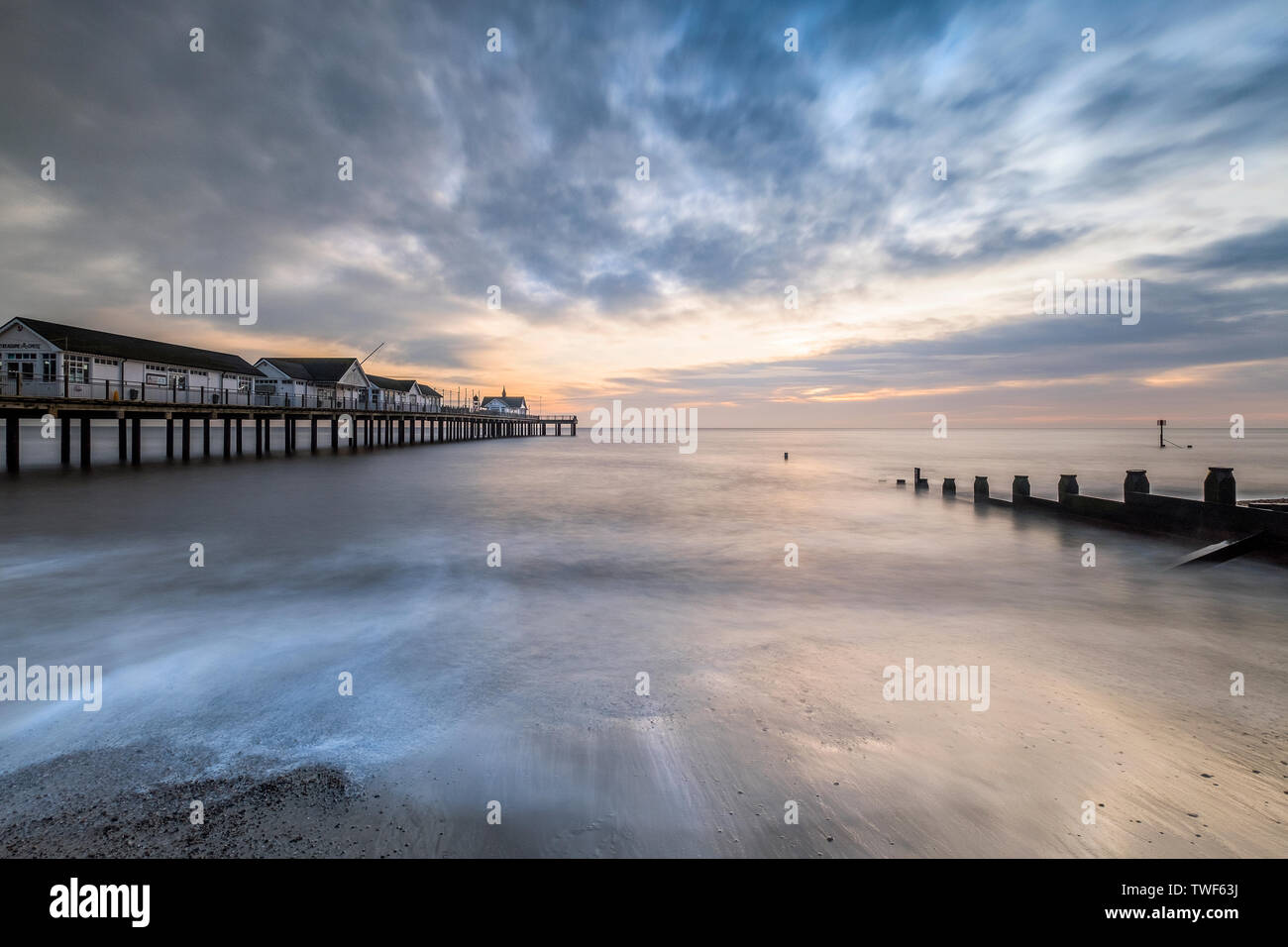 Southwold pier in Suffolk looking in between one of the sea defences on the sandy beach. - Stock Image