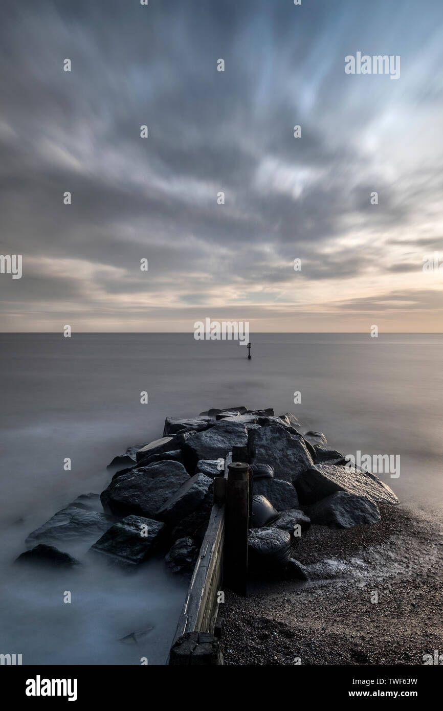 Rock groynes or sea defences to the right of Southwold pier as the sun comes up. - Stock Image