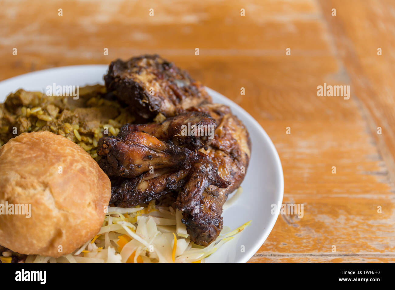 Jamaican food.  Traditional Jamaican curried goat, jerk chicken and fried dumpling with rice and peas. - Stock Image