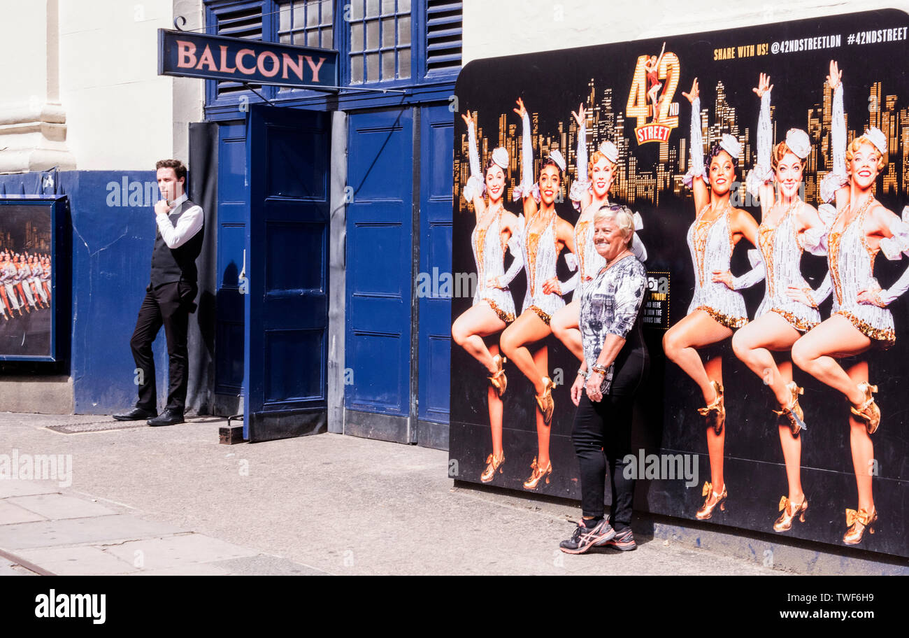 Woman standing in front of poster with female tap dancers advertising 42nd street in London. - Stock Image