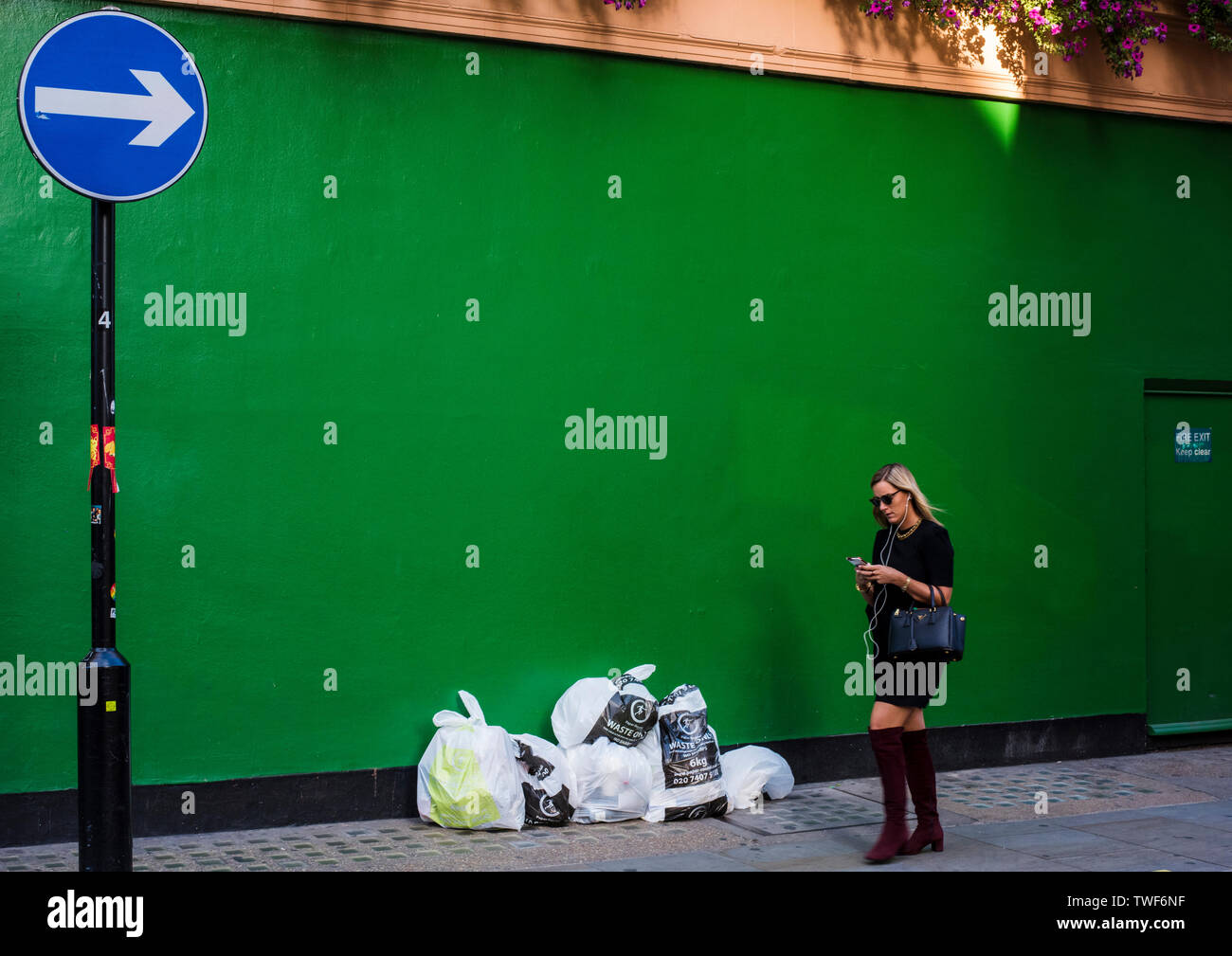 Young woman carrying handbag and using smartphone while walking past green painted wall with rubbish bags in front of it in Central London. - Stock Image