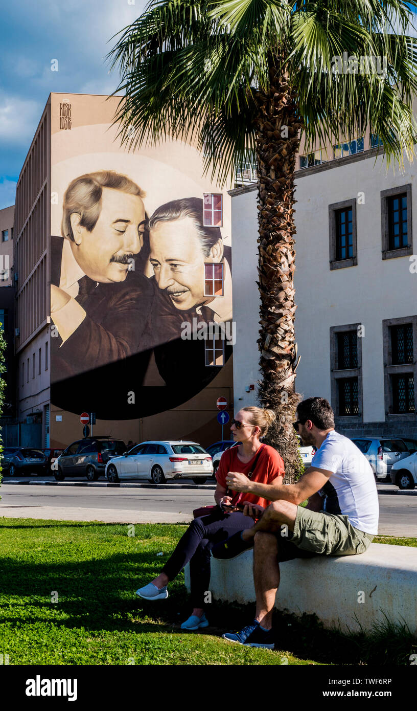 Couple sitting on bench with mural in the background showing famous judges Giovanni Falcone and Paolo Borsellino in Palermo in Sicily. Stock Photo