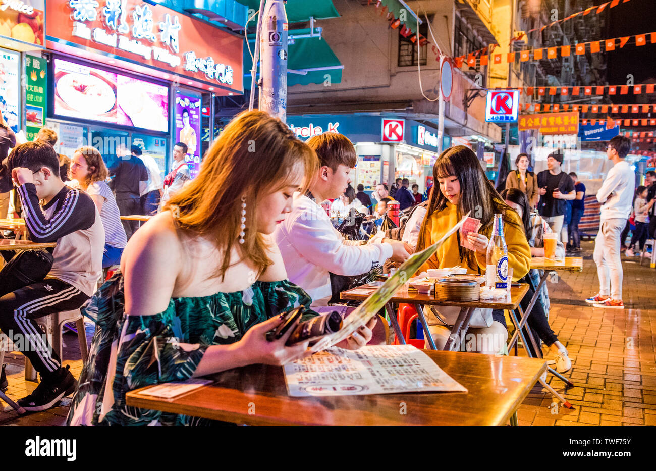 Large group of people relaxing and socialising at Temple Street night market in Hong Kong. - Stock Image
