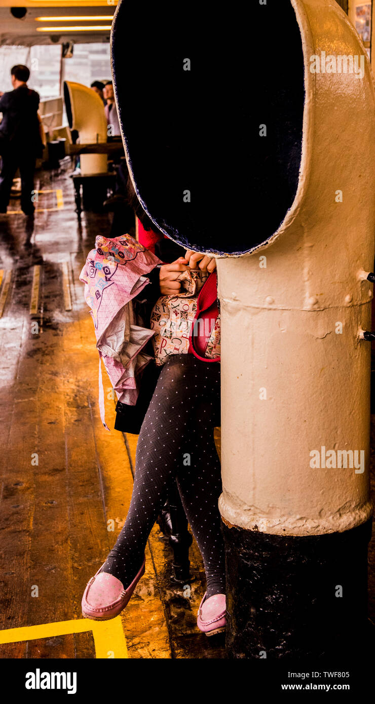 Woman sitting on Star ferry partially obscured by funnel in Hong Kong. - Stock Image