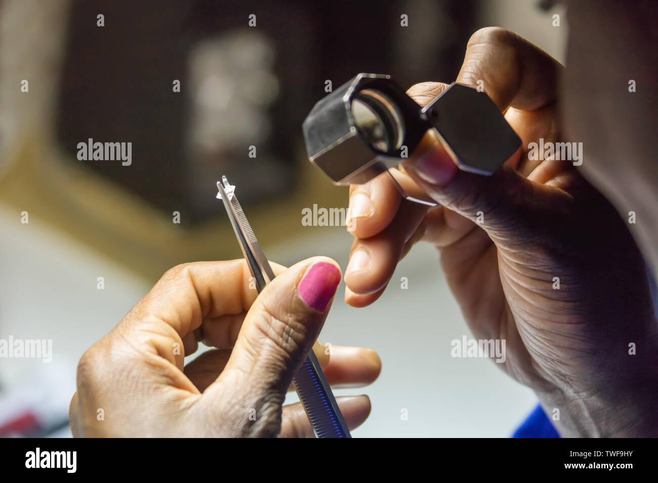 Botswana, african woman worker checking quality of a diamond. - Stock Image