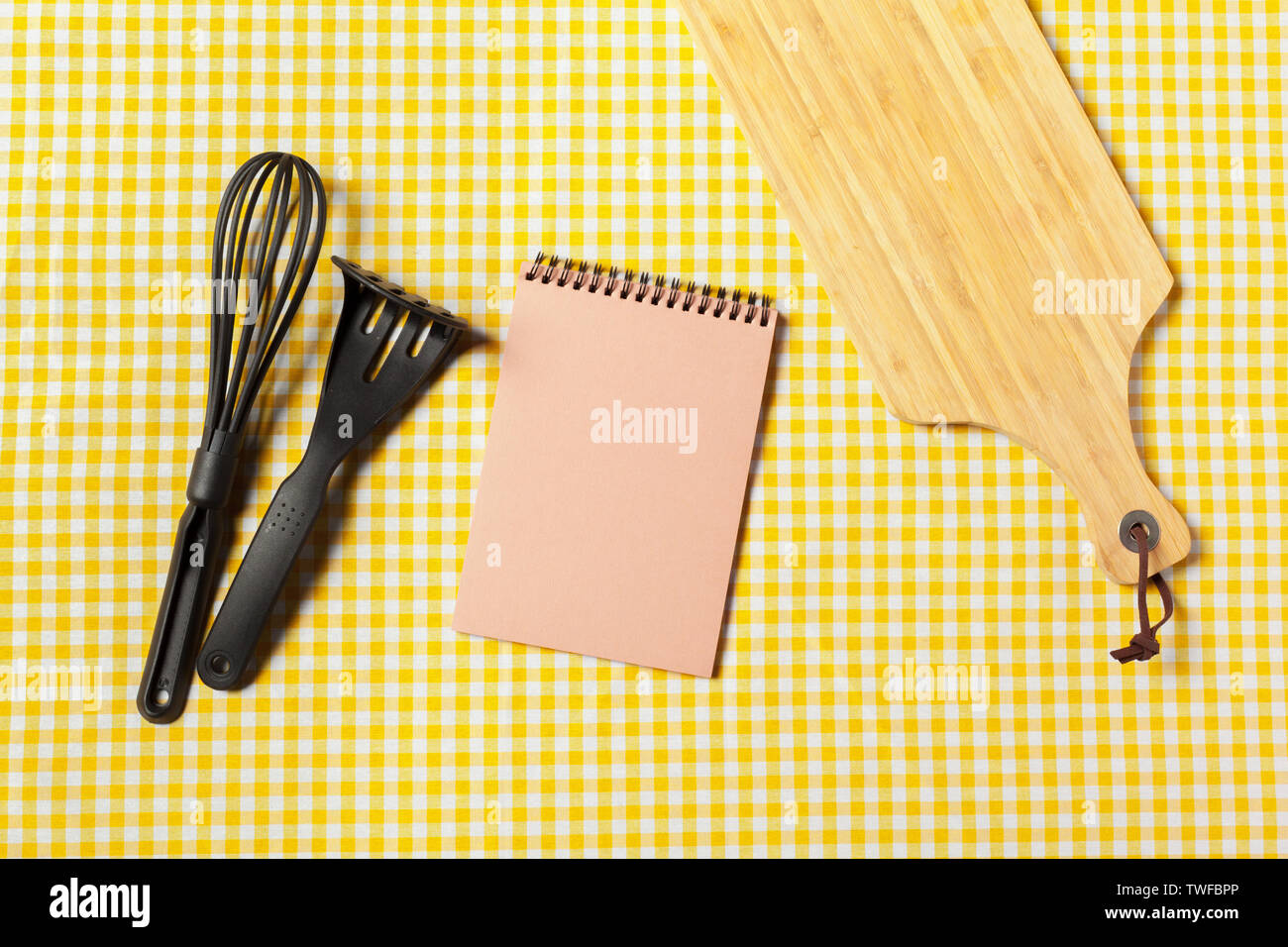 Blank sheet of opened notepad and kitchen utensils on  table with tablecloth, copy space - Stock Image