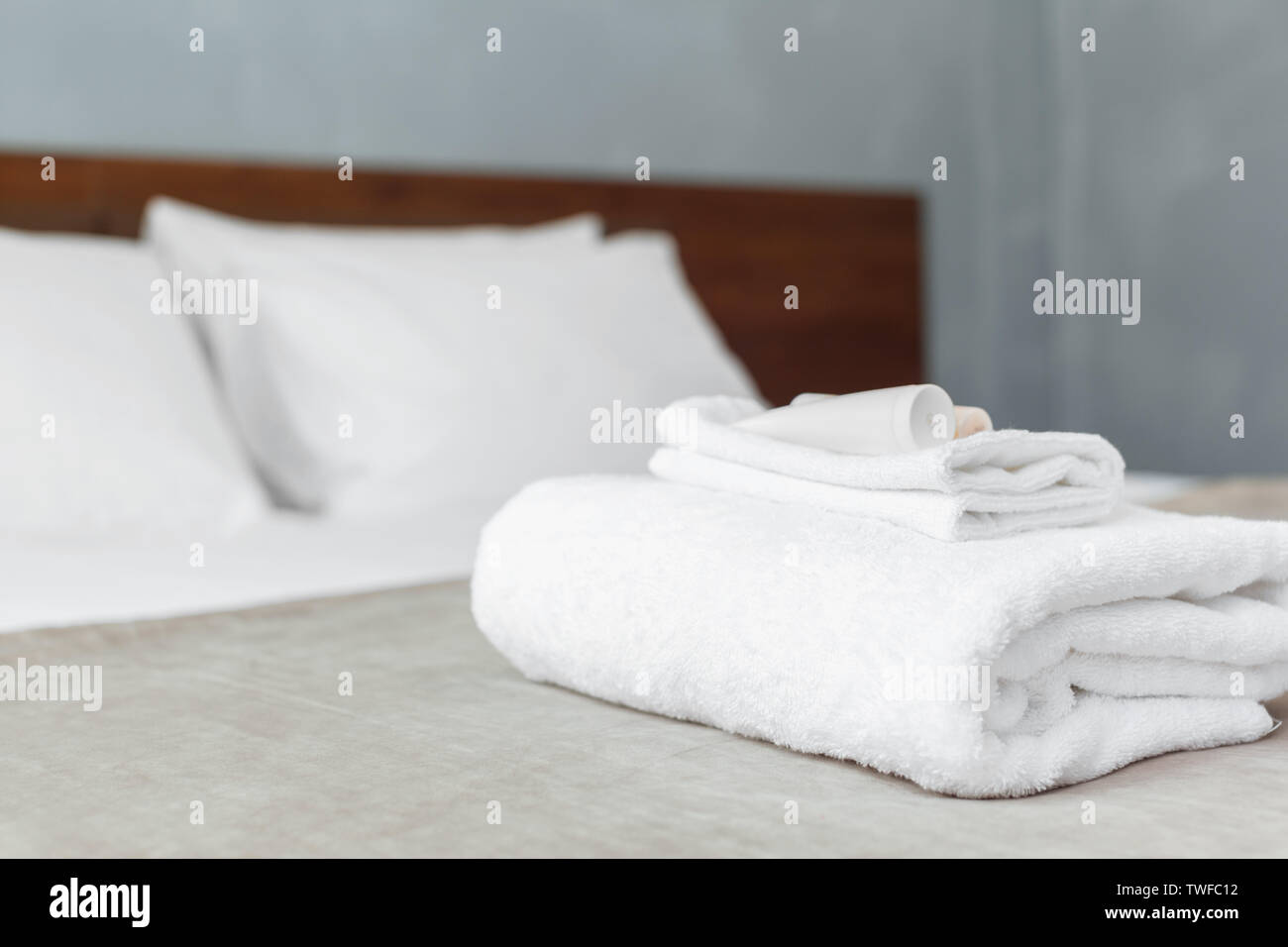 White towel on bed in guest room for hotel customer - Stock Image