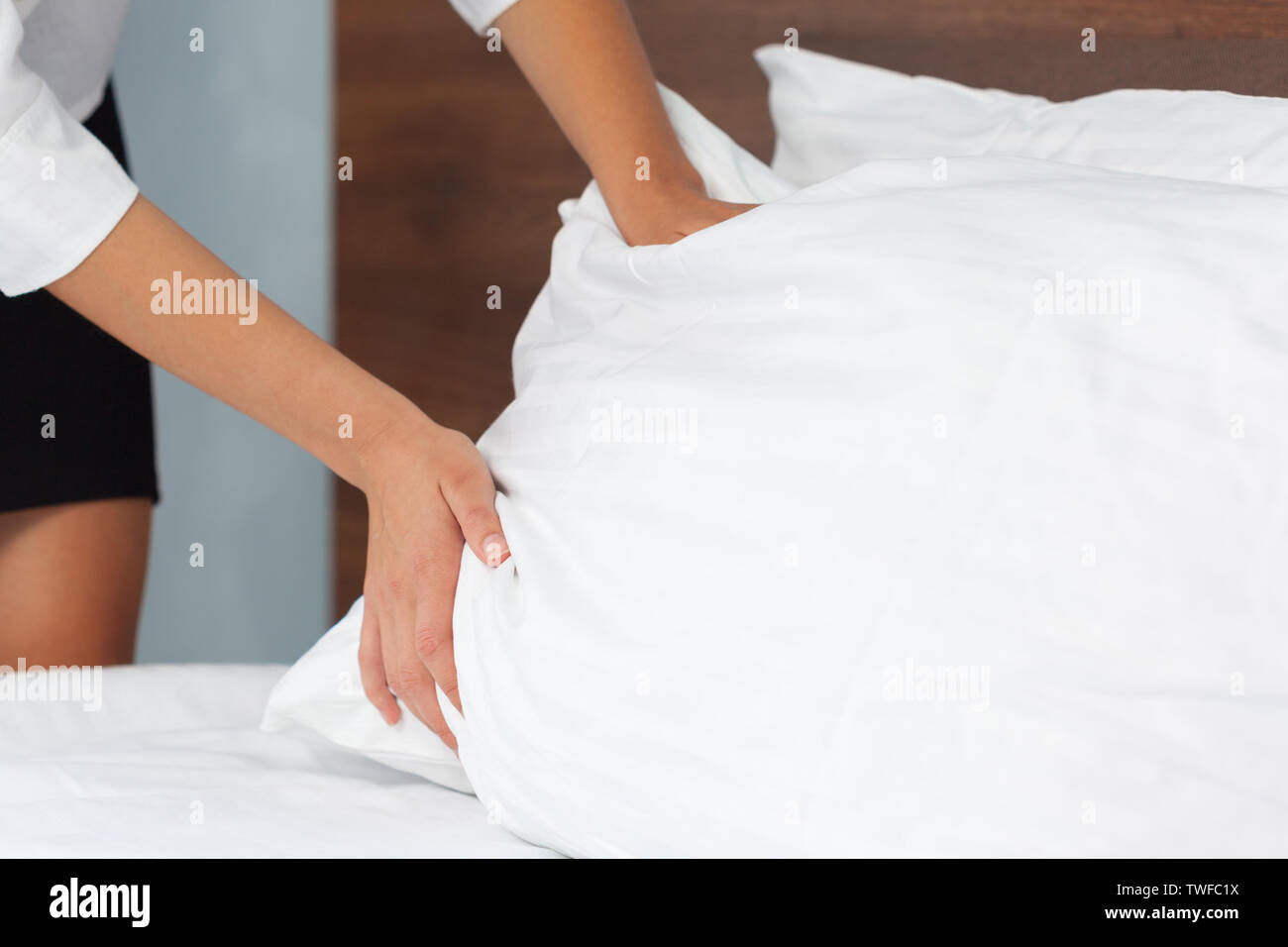 Young maid making bed in hotel room - Stock Image