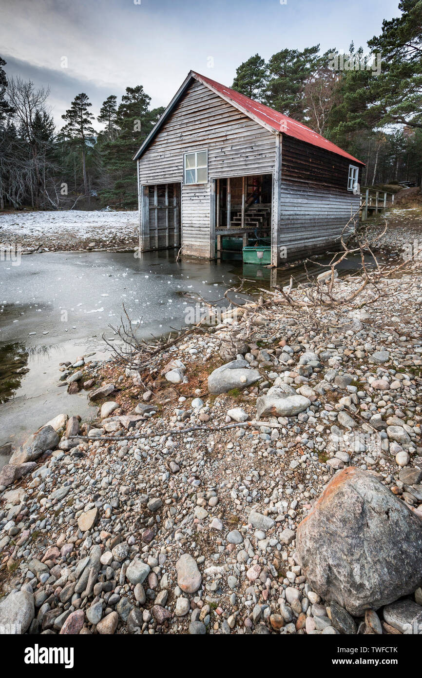 Boathouse on frozen Loch Vaa in the Cairngorms National Park of Scotland. - Stock Image