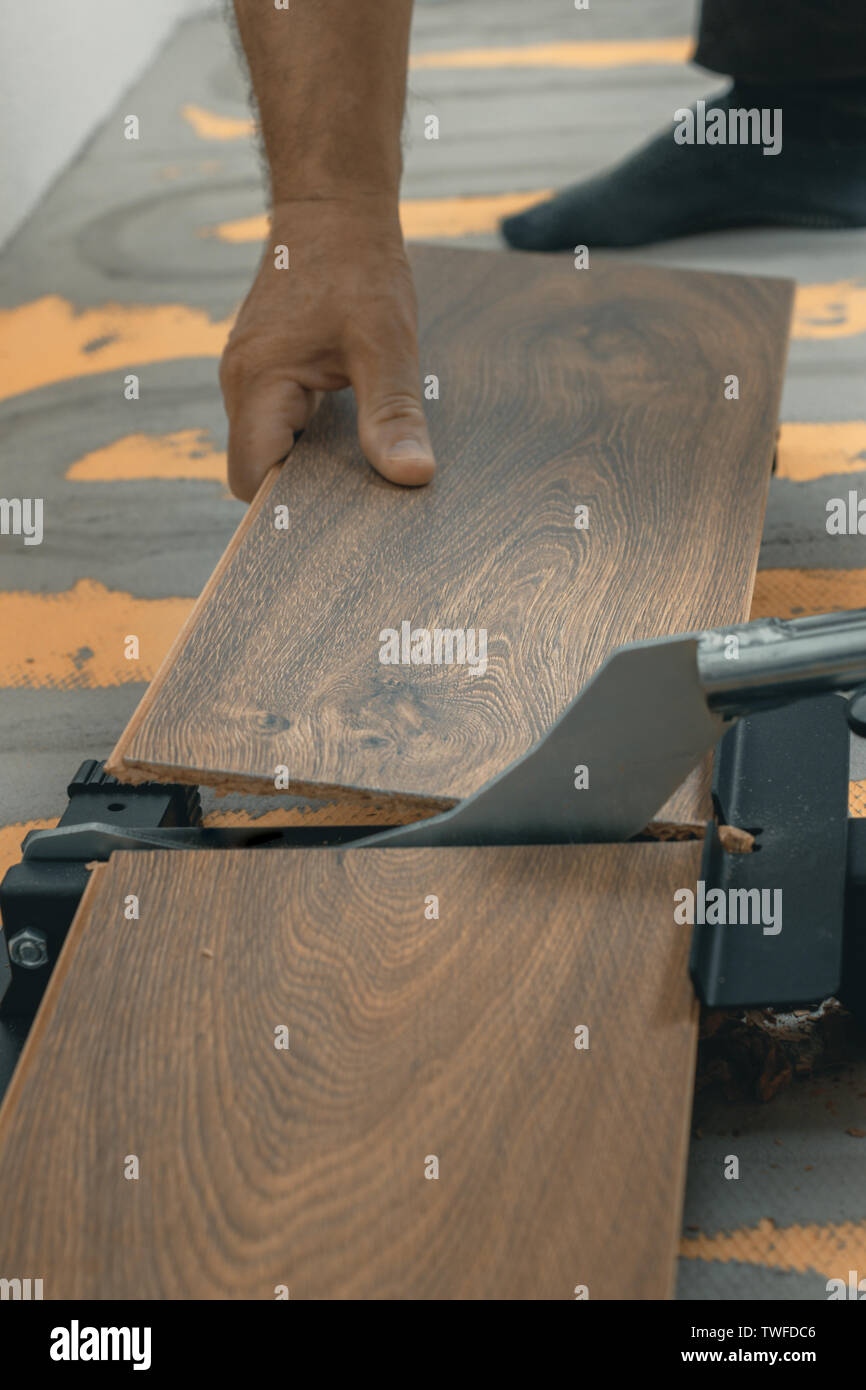 hand holding and cutting the laminate panel with a laminate cutter - Stock Image