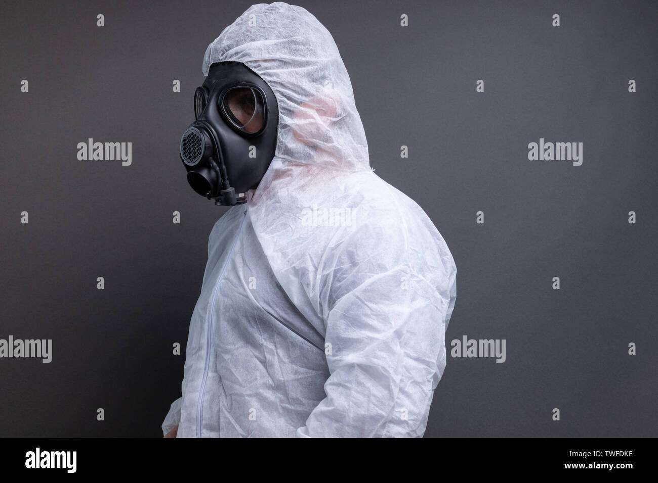 side view of man with gas mask in protective overall suit against grey background - Stock Image