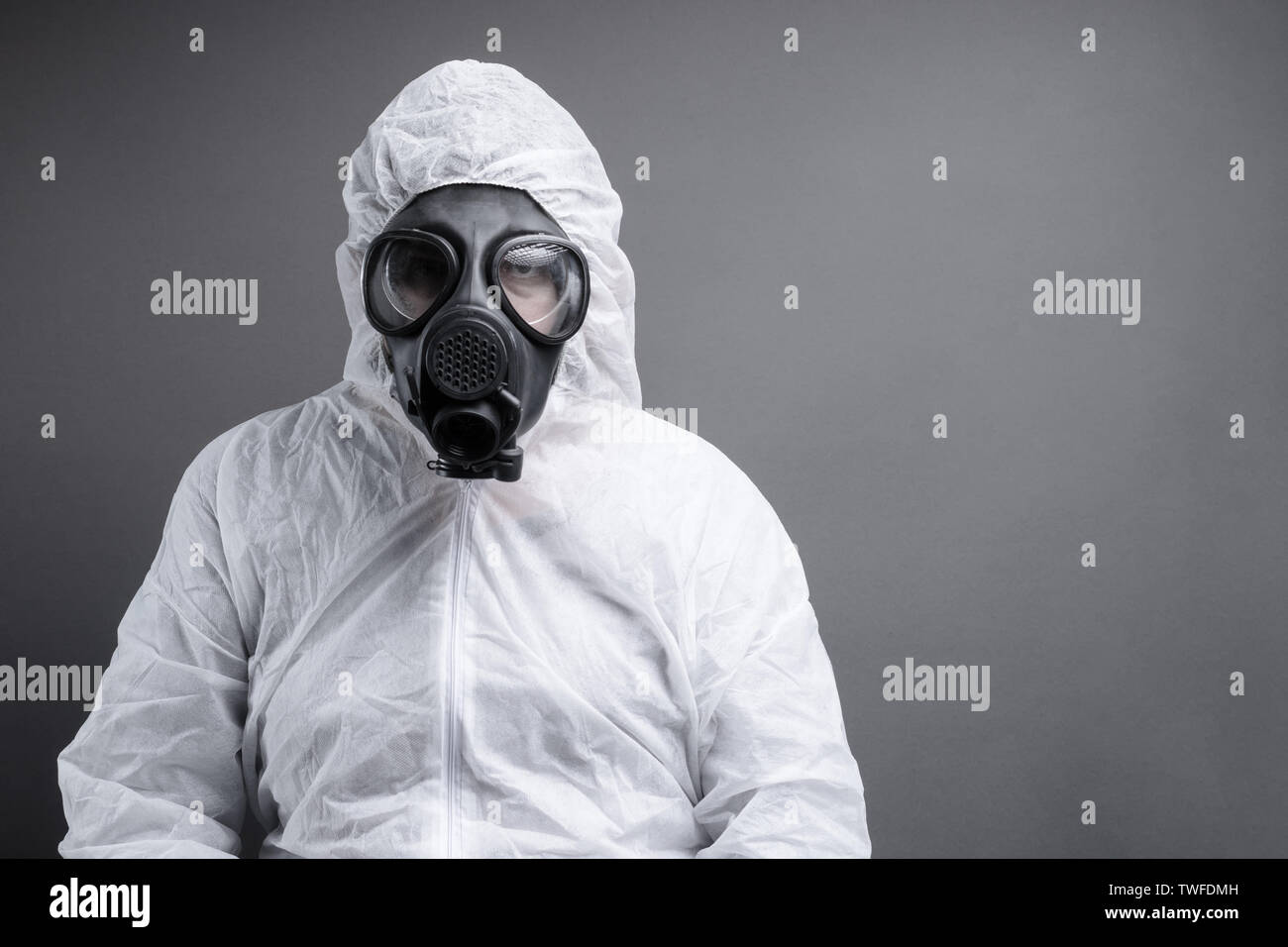 man with gas mask in protective overall suit against grey background - Stock Image