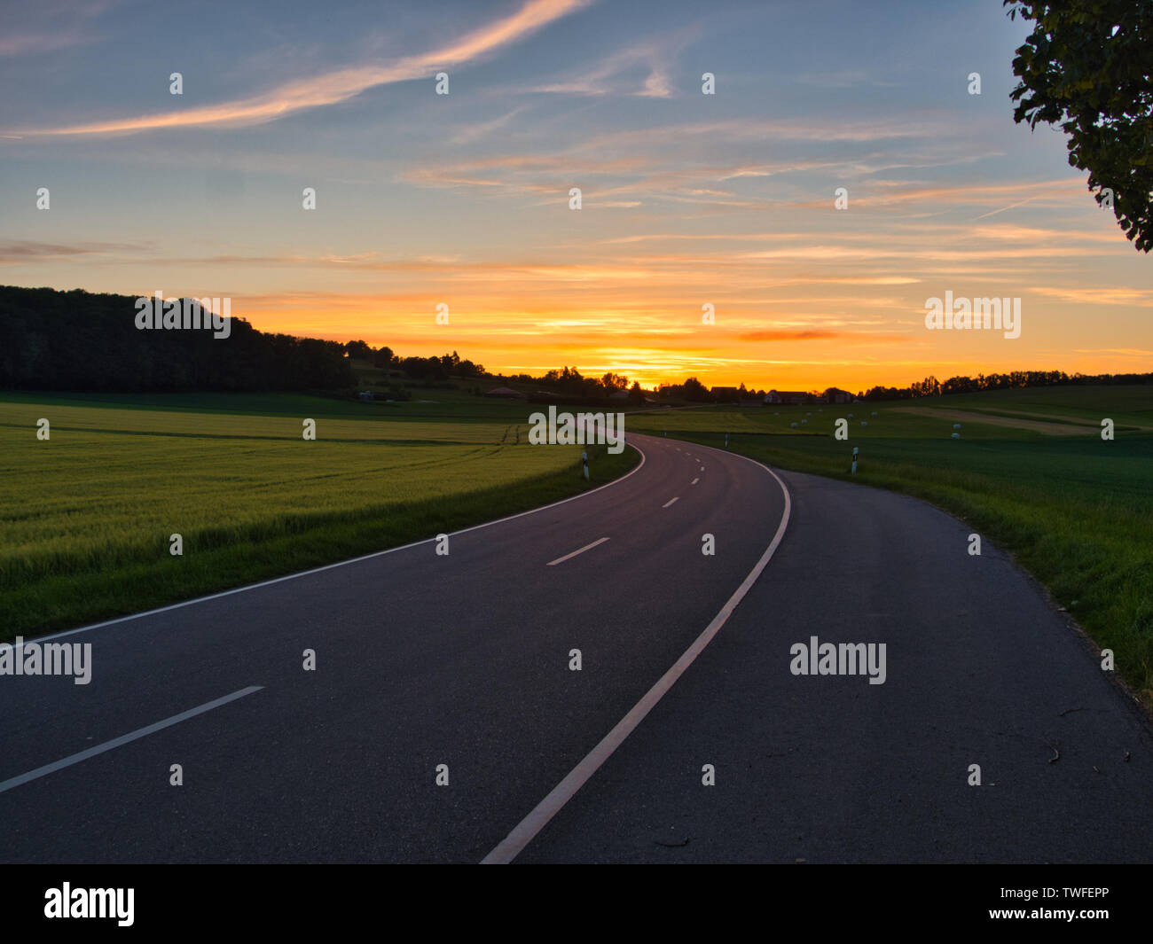 Winding road during golden hour at the Swabien Alb Germany - Stock Image