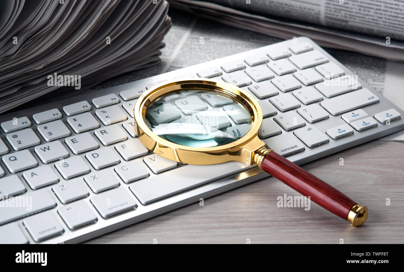magnifier on the keyboard and a stack of newspapers - Stock Image