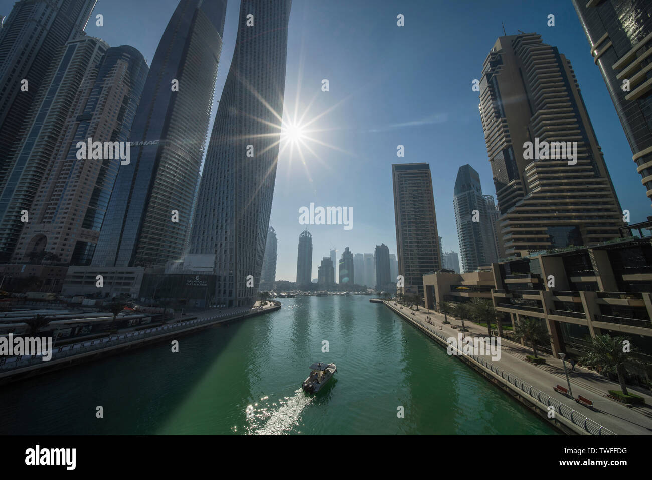 The sun coming up over the Dubai streams light into the marina. - Stock Image