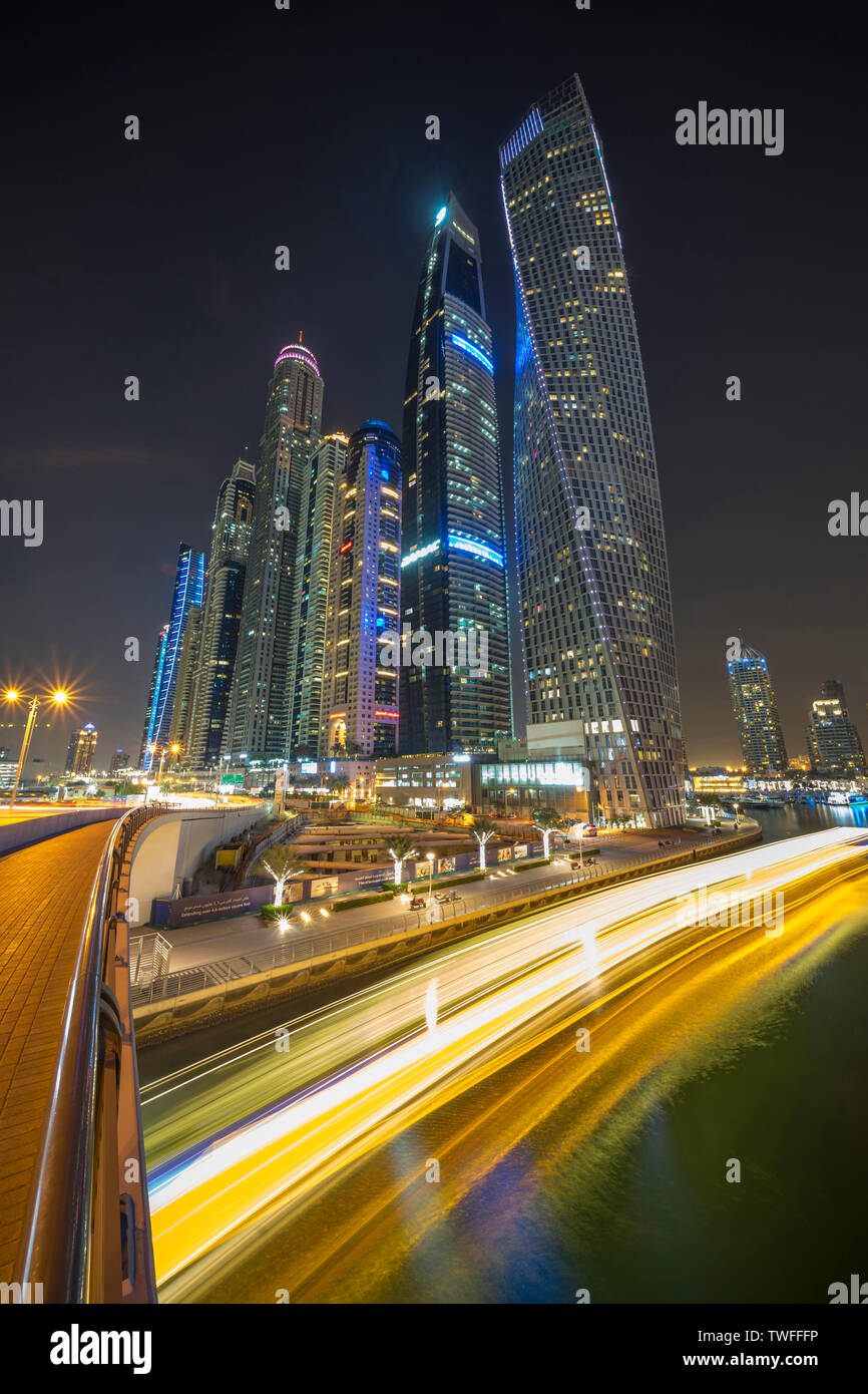 The light trails of a dinner cruise stream past in the Dubai Marina. - Stock Image