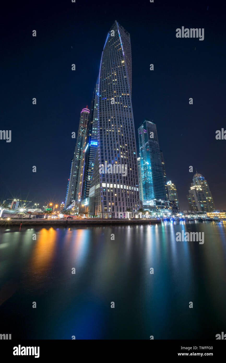 Cayan Tower rising over the shimmering waters of the Dubai Marina. - Stock Image