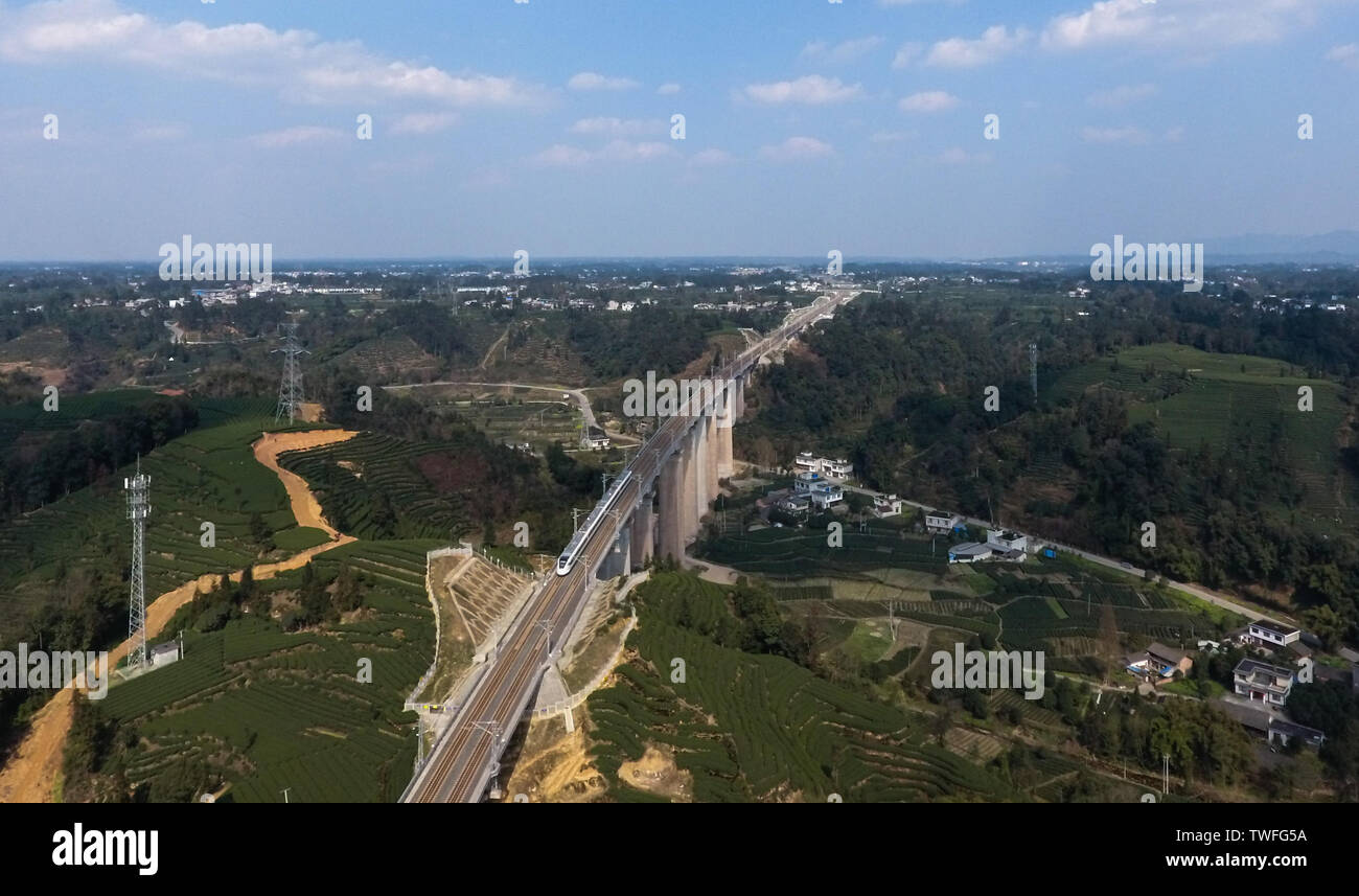 (190620) -- CHENGDU, June 20, 2019 (Xinhua) -- Aerial photo taken on March 11, 2019 shows a train running on the Chengdu-Ya'an railway in Ya'an City, southwest China's Sichuan Province. The Chengdu-Ya'an railway, an important part of the Sichuan-Tibet railway, has a length of 140 kilometers and was put into operation on Dec. 28, 2018. Ya'an, a region connecting the Sichuan basin and the Qinghai-Tibet plateau, played a vital role during the ancient times for the Tea Horse Road between Sichuan and Tibet. As a result, the making of Tibetan tea has been passed down through generations and listed a - Stock Image