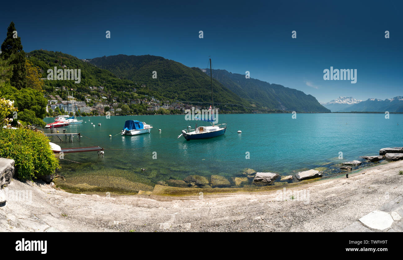 Montreux, VD / Switzerland - 31 May 2019: boats on the shores of Lake Geneva with great view of the Swiss Alps behind as seen from the Montreux Rivier Stock Photo
