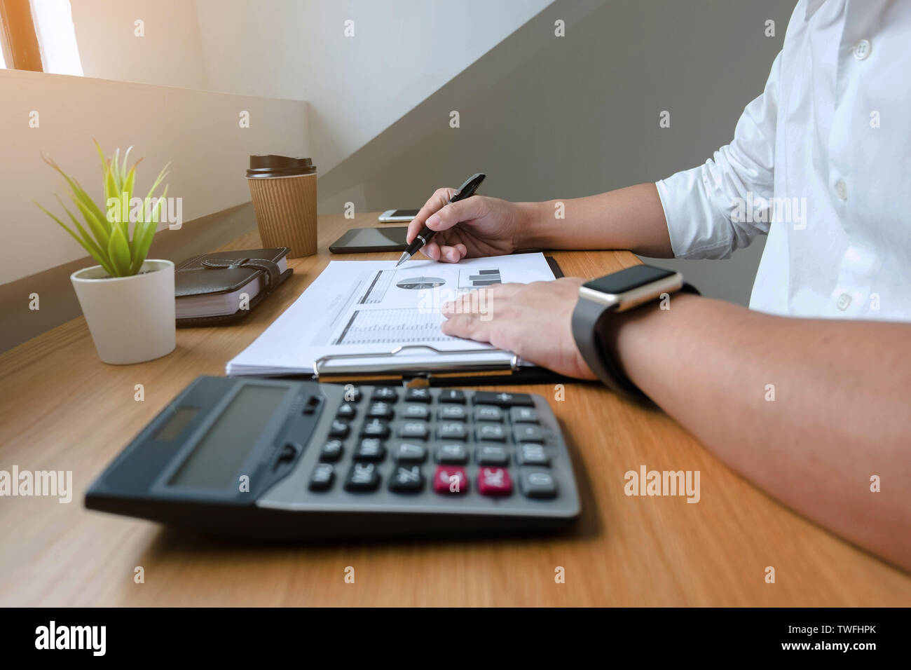 Businessman working with income statement document on the wood table.Business concept. - Stock Image