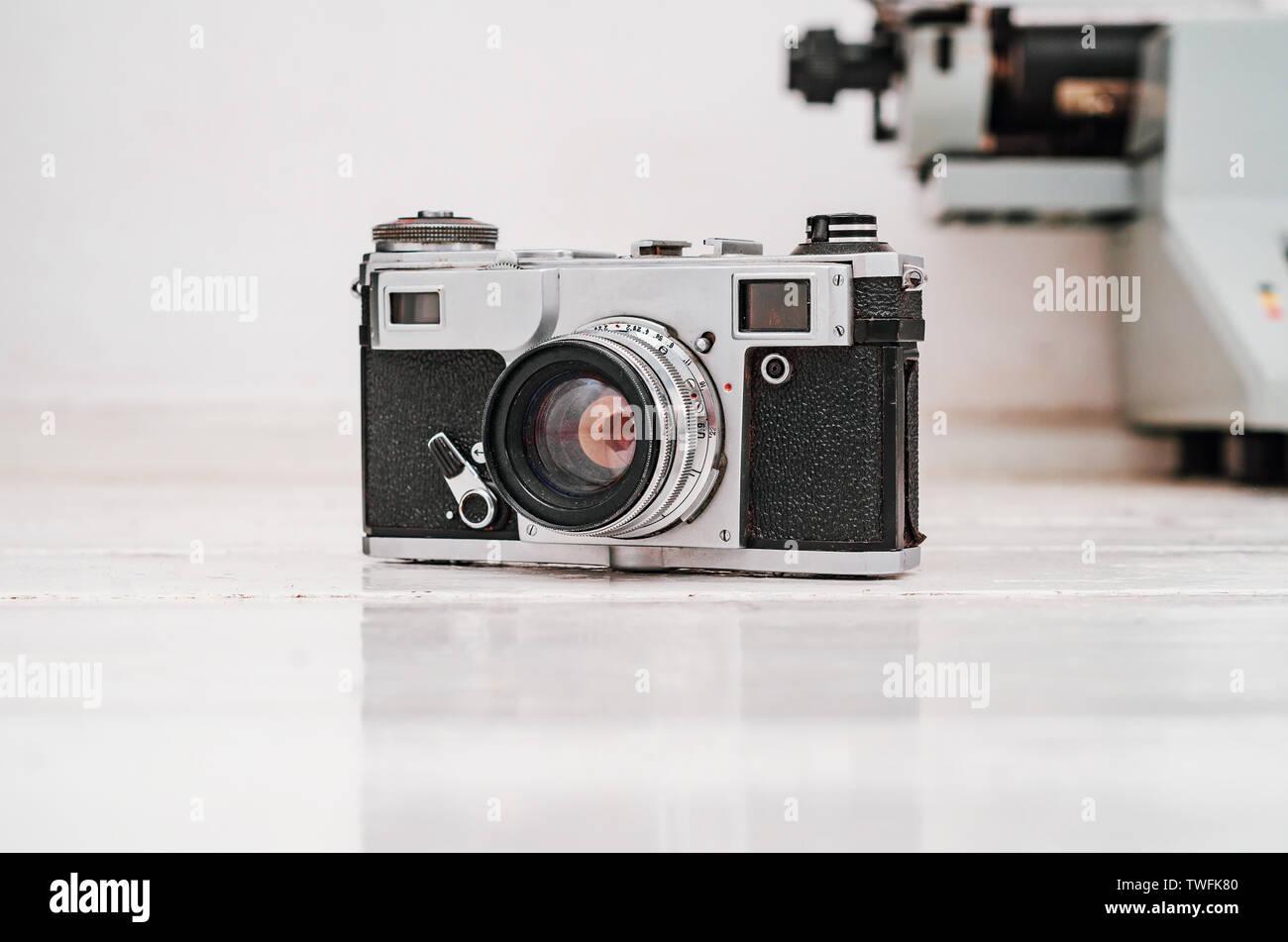 Old film camera on white plank background. Typewriter on the background. Vintage photo. Stock Photo