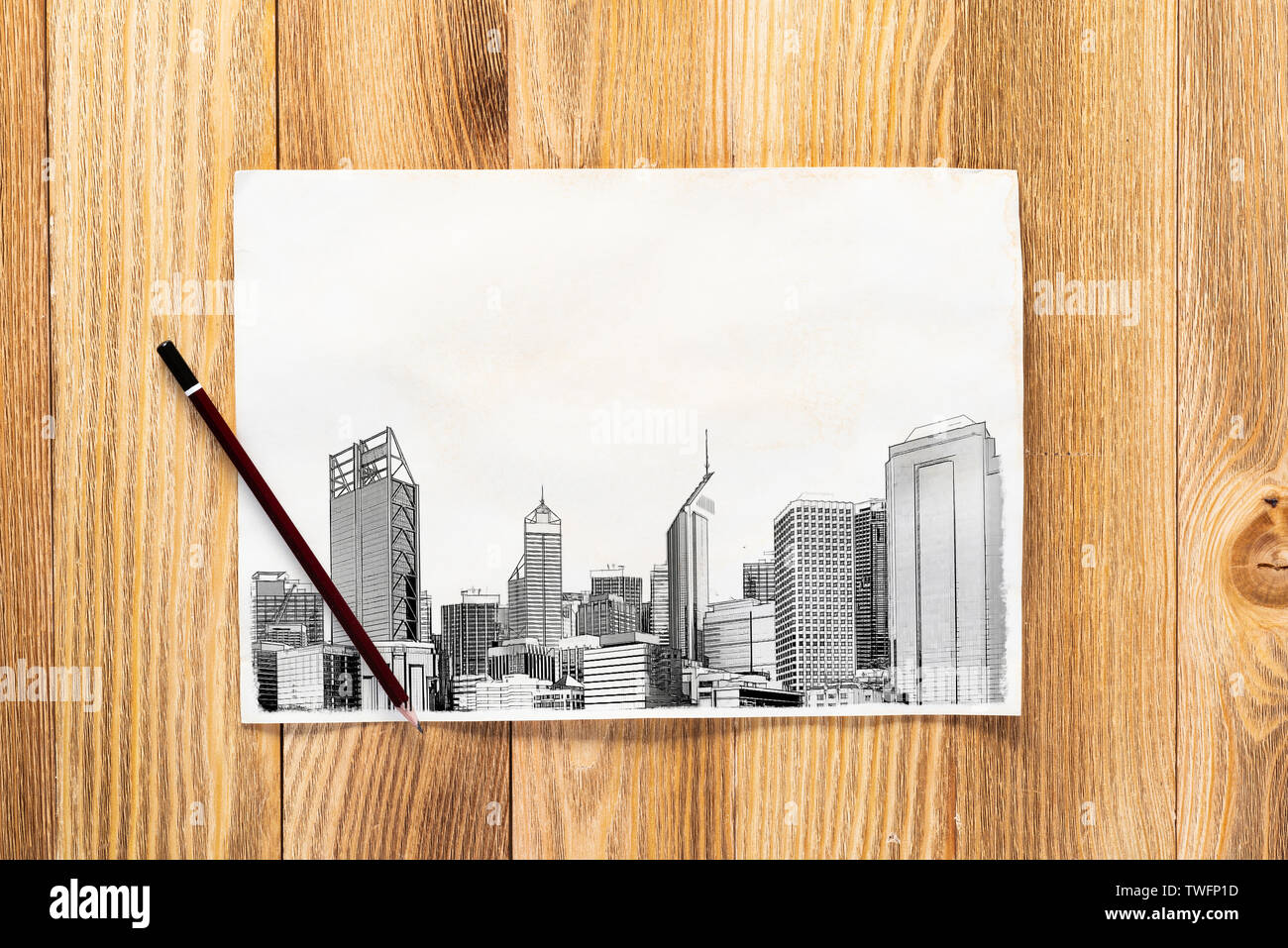 Modern city center pencil draw. Urban architecture hand drawn sketch on wooden table. Sheet of paper on textured natural wooden background. Architectu - Stock Image