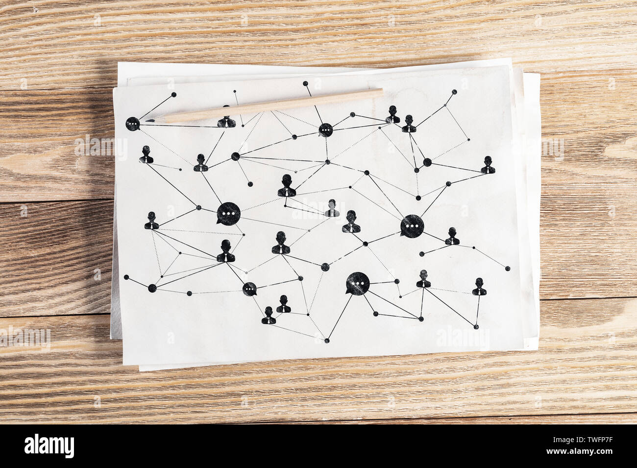 Social network structure pencil hand drawn with human icons and intersections. Business communication sketch on wooden surface. Top view of workplace - Stock Image